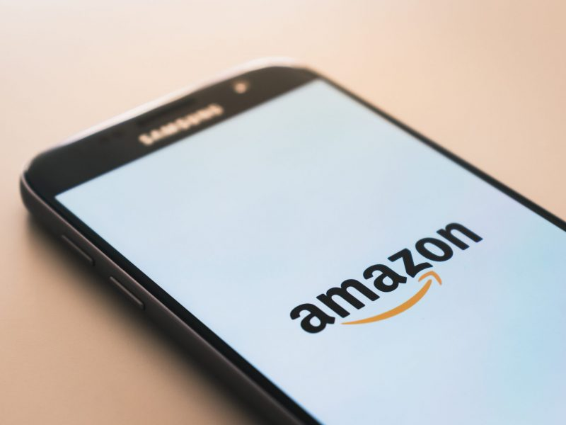 a phone on a desk with amazon app loading