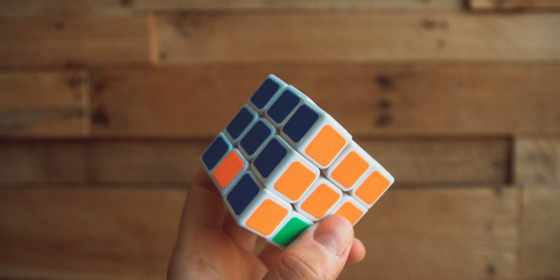 a rubix cube showing a smart person with their hand on the orange and blue part