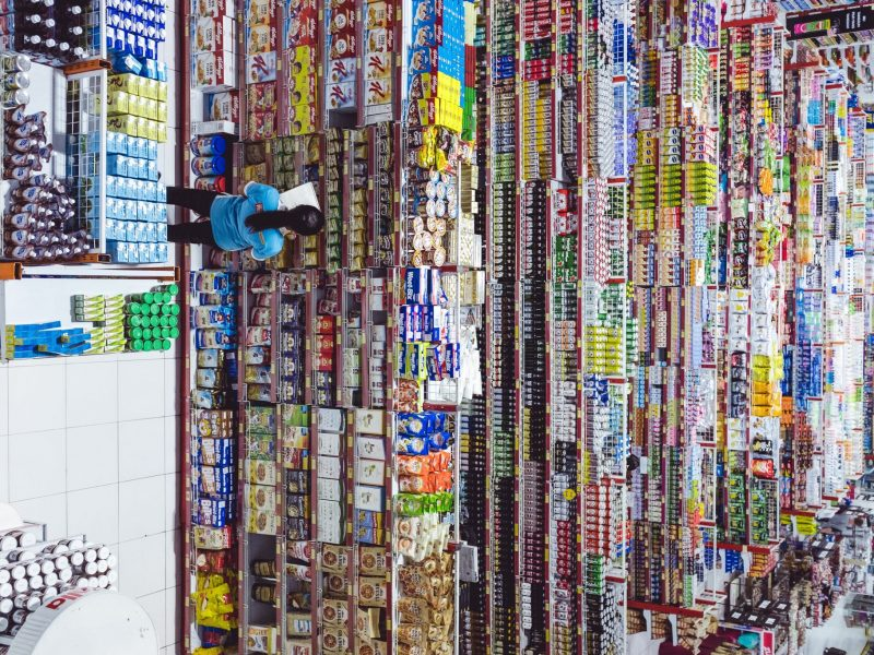 woman standing in front of thousands of products in a store cataloging them